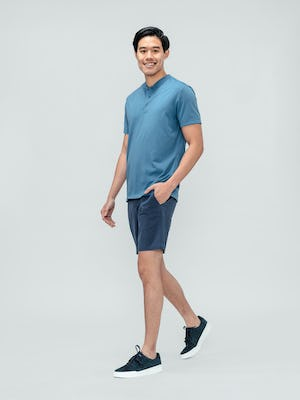 Men's Slate Blue Kinetic Shorts and Men's Storm Blue Composite Merino Short Sleeve Henley on model walking left with hand in pockets