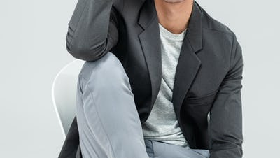 Men's Charcoal Kinetic Blazer over Men's Pale Grey Heather Composite Merino Tee with Men's Light Grey Momentum Chino on model sitting in chair