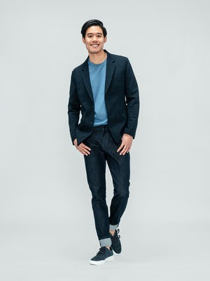 model wearing men's navy kinetic blazer and storm blue composite merino active tee and indigo chroma denim facing forward with thumbs in pockets