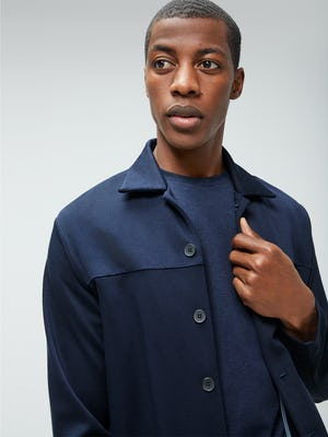 Close up of Men's Navy Composite Merino Tee under Men's Navy Fusion Chore Coat on model adjusting jacket