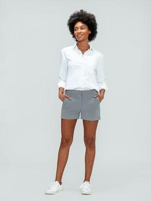 Women's Light Grey Momentum Chino Shorts and White Aero Zero Boyfriend Shirt on model with hands in shorts pockets
