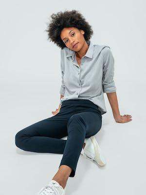 Women's Navy Kinetic Skinny Pant and Grey Heather Apollo Shirt on model sitting on floor