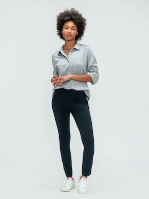 Women's Navy Kinetic Skinny Pant and Grey Heather Apollo Shirt on model adjusting sleeve
