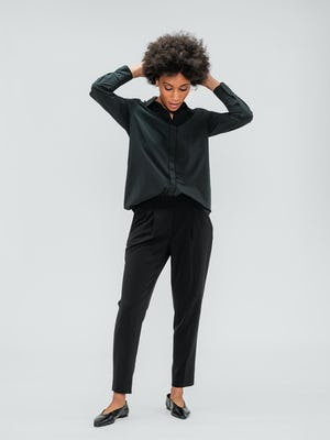 Women's Black Swift Drape Pant and Women's Black Juno Blouse on model playing with hair