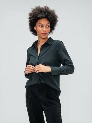 Women's Black Swift Drape Pant and Women's Black Juno Blouse on model adjusting shirt button