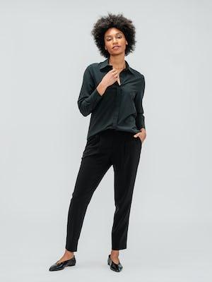 Women's Black Swift Drape Pant and Women's Black Juno Blouse on model adjusting sleeve