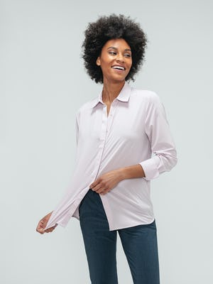 Women's Azurite Heather Velocity Pant and Rose Quartz Juno Blouse on model stretching shirt