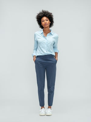 Women's Light Blue Juno Recycled Tailored Shirt and Slate Blue Kinetic Pull-On Pant on model facing forward with hands in pant pockets