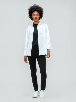 Women's Black Kinetic Skinny Pant and White Aero Zero Boyfriend Shirt on model facing forward with shirt unbuttoned