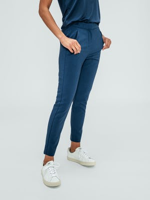 women's indigo heather velocity tapered pant model facing off-center with thumbs in pockets