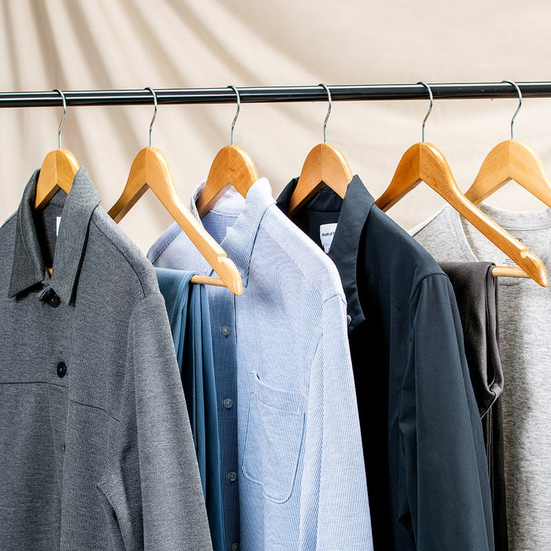 Shirts and sweaters hanging on a clothing rack