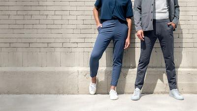 Man and woman standing against a brick wall waring Fusion pants