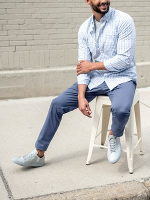 men's indigo heather kinetic jogger and pale grey heather composite merino tee and blue dot matrix aero button down model sitting on stool with sleeves cuffed