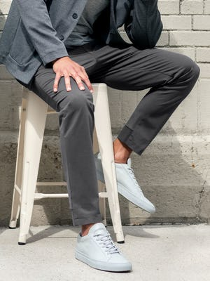 men's charcoal kinetic jogger and pale grey heather composite merino tee and charcoal fusion chore coat on model sitting on stool with one leg up