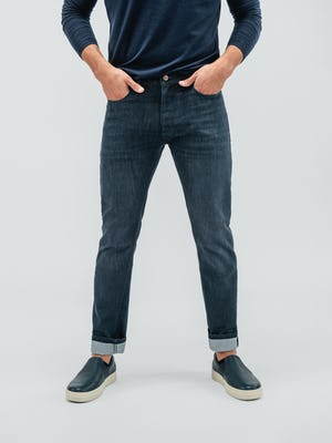 model wearing indigo fade chroma denim and navy composite long sleeve tee facing forward with hands in pockets