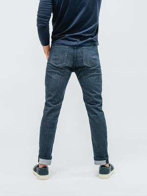 model wearing indigo fade chroma denim and navy composite long sleeve tee facing away