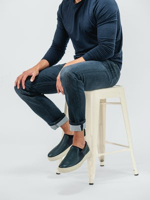 model wearing indigo fade chroma denim and navy composite long sleeve tee sitting on a stool with legs cuffed