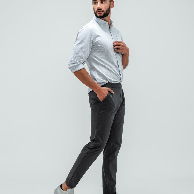 Man wearing the Kinetic Jogger Pants in Charcoal and the Hybrid Button Down Shirt in Grey Stripe