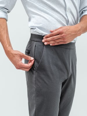 Close up shot of a man zipping up the side pocket on a pair of kinetic jogger pants in indigo heather