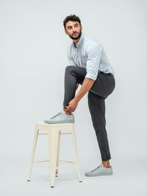 Man wearing a hybrid button down shirt in grey stripe and the kinetic jogger pants in charcoal with grey sneakers