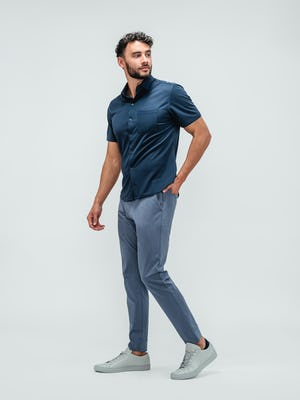Man wearing an apollo short sleeve button up shirt in navy and kinetic jogger pants in indigo heather with grey sneakers