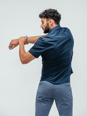 Man facing away from camera stretching his right arm across his chest and wearing an apollo short sleeve button up shirt in navy