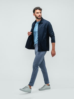 Man stretching his right leg and wearing kinetic jogger pants in indigo heather, a composite active tee in chambray blue, and a fusion chore coat in navy