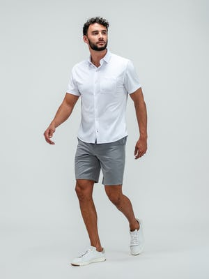 Man wearing pace chino shorts in light grey and the apollo short sleeve button up shirt and white sneakers