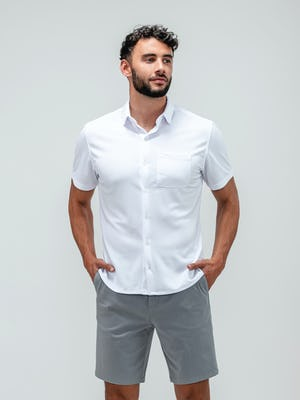 Man with hands in his pockets wearing pace chino shorts in light grey and the apollo short sleeve button up shirt