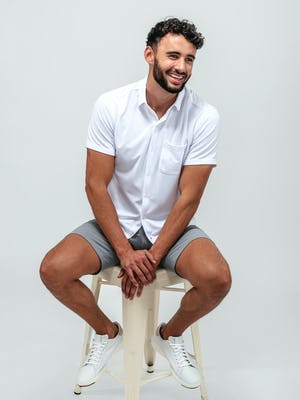 Man sitting on a tan stool wearing pace chino shorts in light grey and the apollo short sleeve button up shirt