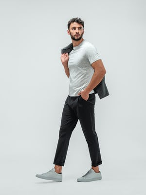 Man wearing the Momentum Tapered Chino Black, Composite Short Sleeve Tee Pale Grey Heather, and Fusion Chore Coat Charcoal with grey sneakers