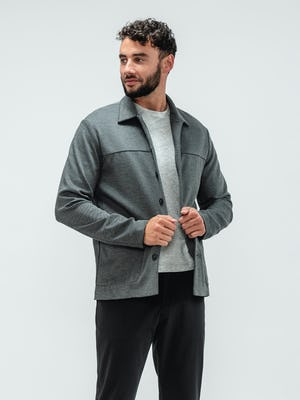 Man wearing the Momentum Tapered Chino Black, Composite Short Sleeve Tee Pale Grey Heather, and Fusion Chore Coat Charcoal