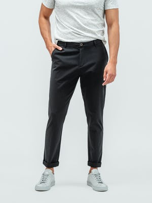 Man with his hand in pocket wearing the pace tapered chino in black with grey sneakers