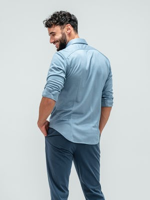 Man facing away from camera and looking over shoulder wearing the slate blue apollo long sleeve raglan shirt