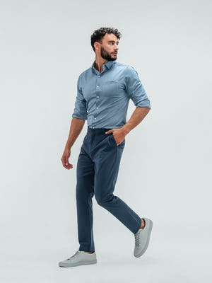 Man wearing the Pace Tapered Chino in Faded Indigo and the Apollo Long Sleeve Raglan Shirt with grey sneakers