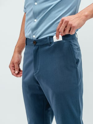 Close up shot of a man putting a pair of airpods in the front pocket of a pair of Pace tapered chino pants in faded indigo