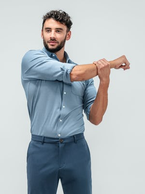 Man stretching his right arm across his chest and wearing the Apollo long sleeve raglan shirts in slate blue
