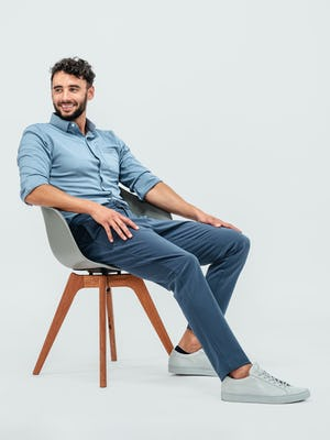 Man wearing the Pace Tapered Chino in Faded Indigo and the Apollo Long Sleeve Raglan shirt in Slate Blue and sitting in a grey chair and wearing grey sneakers