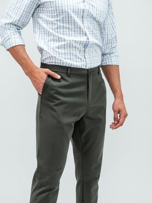 Man standing facing the camera with a hand in his pocket and wearing the olive pace tapered chino pants