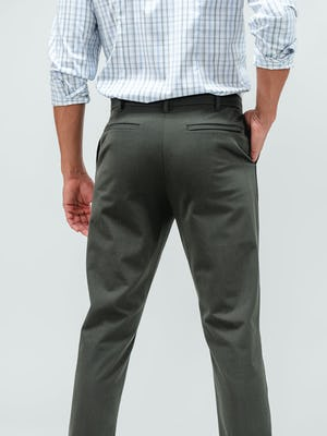 Man standing facing away from the camera with a hand in his pocket and wearing the olive pace tapered chino pants