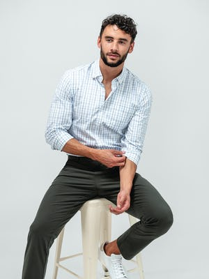 Man wearing the Pace Tapered Chino in Olive and the Aero Button Down in Grey Blue Plaid and sitting on a tan stool