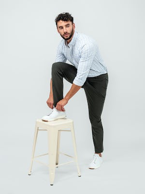 Man wearing the Pace Tapered Chino in Olive and the Aero Button Down in Grey Blue Plaid while tying his shoe and leaning on a tan stool