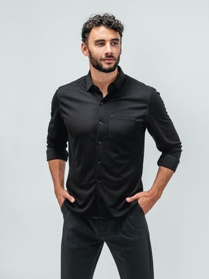 Man wearing the apollo long sleeve raglan shirt in black and standing with his hands in his pockets