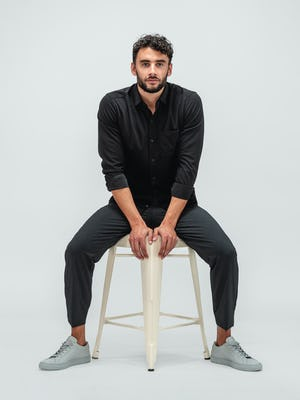 Man wearing the Velocity Pant Dark Charcoal and Apollo Long Sleeve Raglan shirt in Black while wearing grey sneakers and sitting on a tan stool