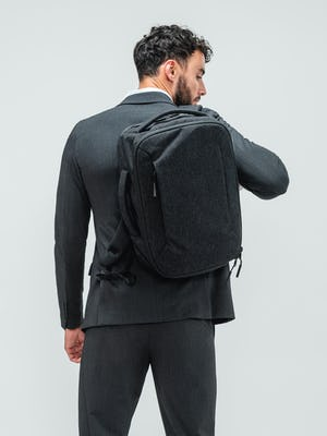Man facing away from camera wearing the dark charcoal velocity suit and with the grey aer collaboration backpack slung over one shoulder
