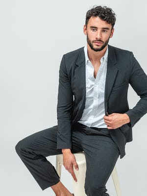 Man wearing Velocity Pant Dark Charcoal, Hybrid Button Down Grey Stripe and Velocity Blazer Dark Charcoal and sitting on a tan stool