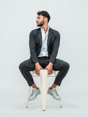 Man wearing Velocity Pant Dark Charcoal, Hybrid Button Down Grey Stripe and Velocity Blazer Dark Charcoal with grey sneakers and sitting in a grey chair