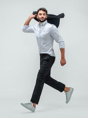 Man wearing Velocity Pant Dark Charcoal, Hybrid Button Down Grey Stripe, Velocity Blazer Dark Charcoal and grey sneakers