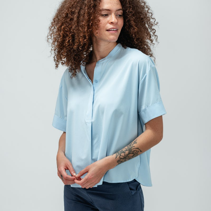 Woman with curly hair wearing chambray blue short sleeve juno boxy blouse