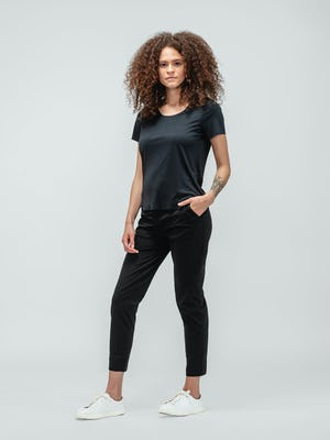 Woman with curly hair wearing black short sleeve luxe touch tee and black kinetic pull on pants and white sneakers